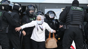 An elderly woman is arrested by police as thousands of people take to the streets of Minsk