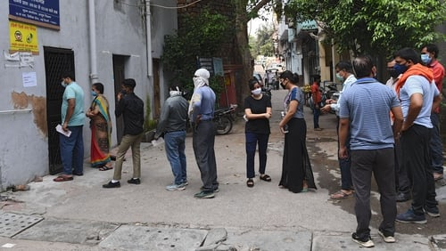 People stand in line as they wait for their coronavirus test in New Delhi, India