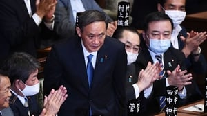 Yoshihide Suga takes the applause in parliament after being voted in as prime minister