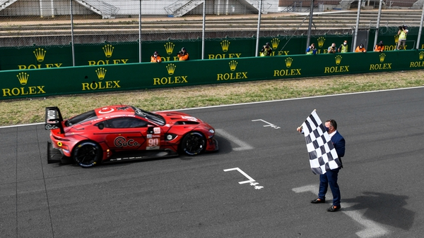 The Aston Martin car takes the checkered flag