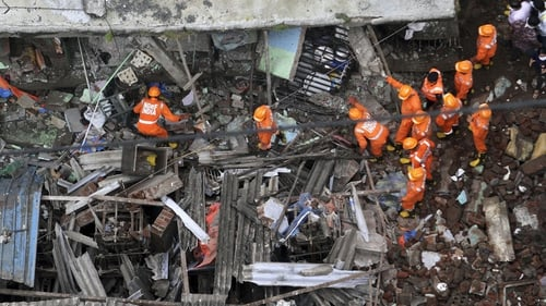 Rescue workers search for survivors in the rubble of a collapsed three-storey residential building in Bhiwandi