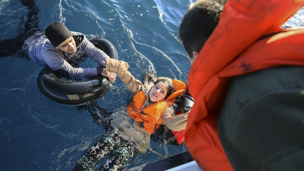 Turkish Coast Guard personnel help refugees en route to Greece in January 2016 (File photo)