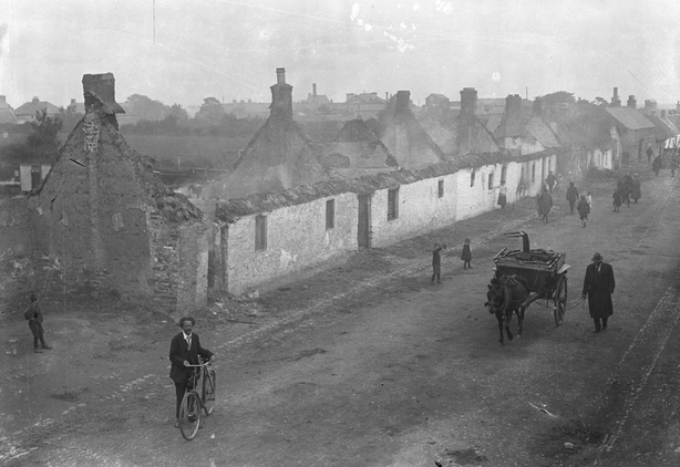 Roofless cottages in Clonard Street, Balbriggan, County Dublin, in the wake of the sack of that village after an attack by the Black and Tans on 20 September 1920. There is a man leading a horse and cart loaded with furniture on the right of shot. Photo: RTÉ Archives 0505/077
