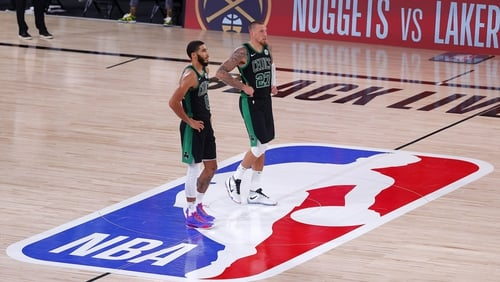Jayson Tatum and Daniel Theis of the Boston Celtics react after their win