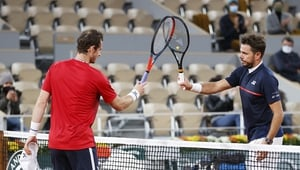 Stan Wawrinka of Switzerland (R) knocks racquets with Andy Murray of Great Britain as part of Covid-19 precautions following victory