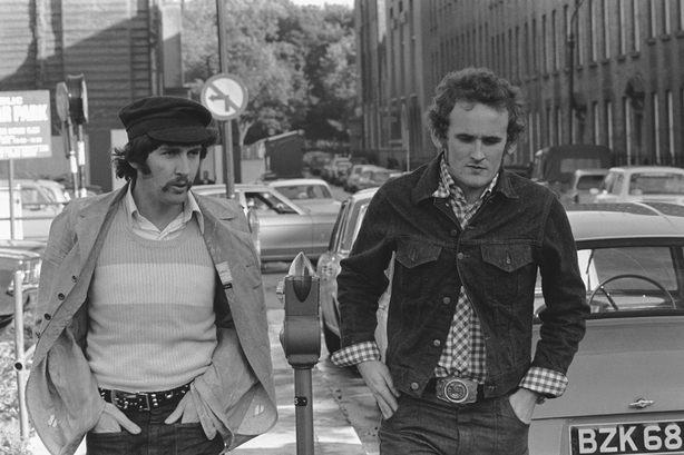 Frank Melia as Hairoil (left) and Colm Meaney as Freddie check for unlocked car doors in a scene from the RTÉ Television production of 'Hatchet', during location filming on York Street, Dublin, in September 1973. A public car park is partly visible on the left of shot.