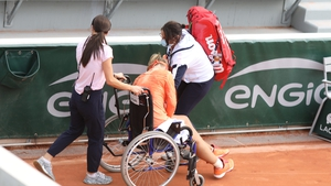 Kiki Bertens is taken off the court in a wheel chair
