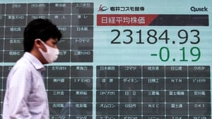 A man walks past a blank electronic board usually displaying Tokyo Stock Exchange share prices after trading was halted due to a glitch today