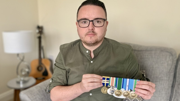Ciaran O'Neill holds up army medals that were presented to him by his father after his coronavirus battle