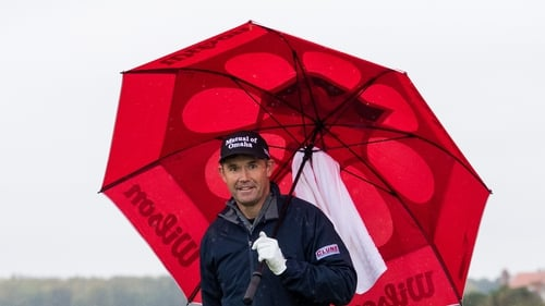 Padraig Harrington protects himself from the elements on day three
