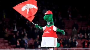 Gunnersaurus, the Arsenal mascot, on the pitch at the Emirates Stadium in London
