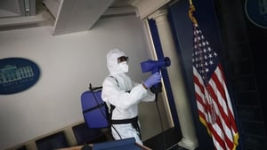 A member of the White House cleaning staff sanitizes the James S Brady Press Briefing Room