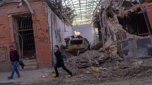 Local residents walk in a street after it was hit by a missile in Gandja, Azerbaijan