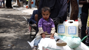 A Yemeni child from a family who was affected by more than 4-years of conflicts, sits on a food ration received from the World Food Programme