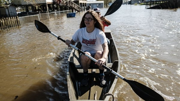 Locals paddle through a flooded road in Delcambre, Louisiana, today