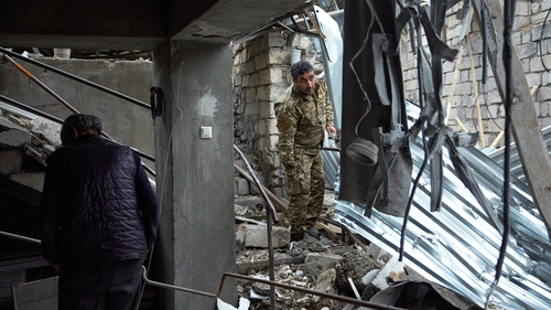 An Armenian soldier is seen in the wreckage of a home damaged by Azeri artillery in Stepanakert