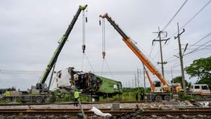 The damaged freight train is removed from the crash site