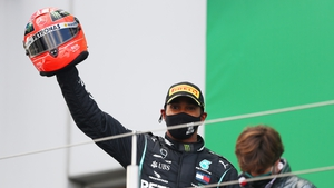 Lewis Hamilton celebrates on the podium after being presented with one of Michael Schumacher's helmets
