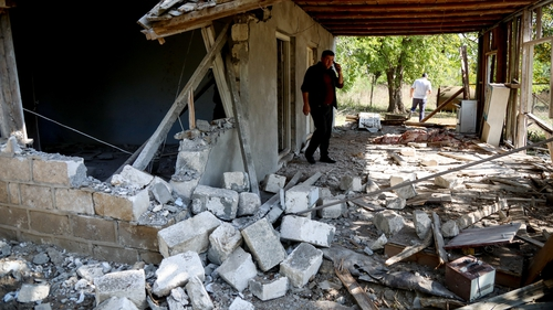 A man looks through the remains of a home that was damaged by Armenian artillery in Tartar, Azerbaijan