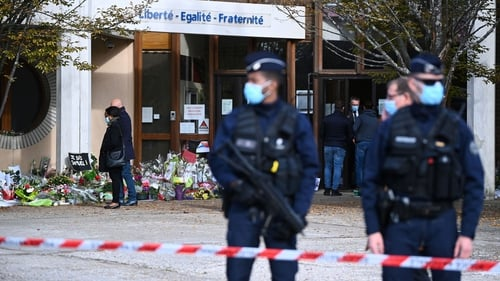 People look at flowers outside the Bois d'Aulne secondary school in Conflans-Sainte-Honorine, northwest of Paris, today