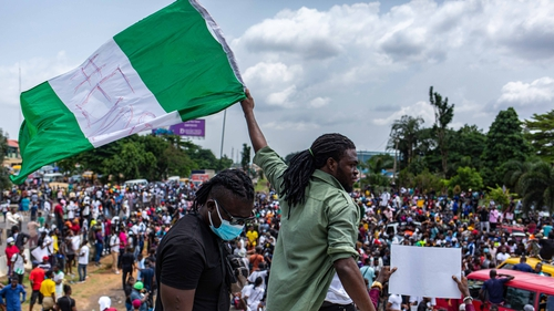 A Nigerian youth waves the Nigerian national flag in protest against the Special Anti-Robbery Squad (SARS) in Lagos last October.