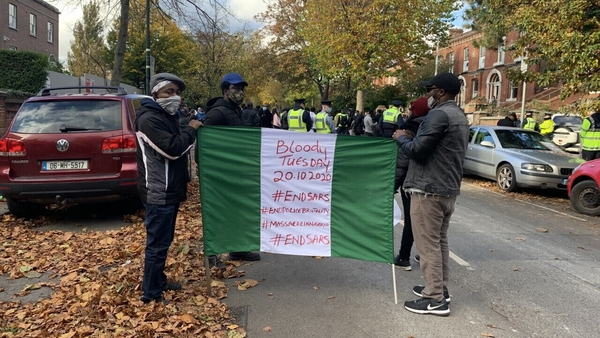 The protesters are ringing bells and waving Nigerian flags outside the embassy in Dublin
