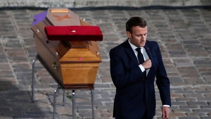 French President Emmanuel Macron pays his respects by the coffin of Samuel Paty