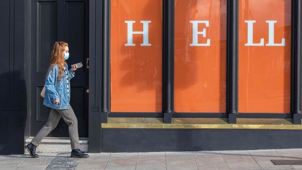 A woman walks past a store in Dublin the day before Ireland begins a second national lockdown. Photo: Paul Faith/AFP via Getty Images