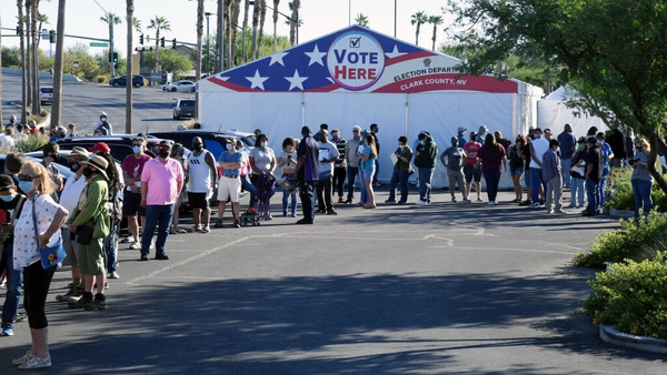 People queue to vote at a shopping centre on the first day of in-person voting on 17 October in Las Vegas, Nevada