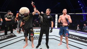 Khabib Nurmagomedov has his arm raised in victory, possibly for the final time, as he calls time on his UFC career