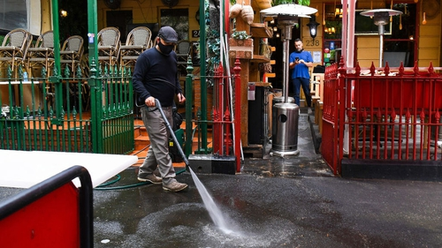 A man cleans as restaurants and cafes prepare for opening in Melbourne