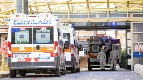 Health workers wearing protective suits and ambulances at the Umberto I hospital in Rome