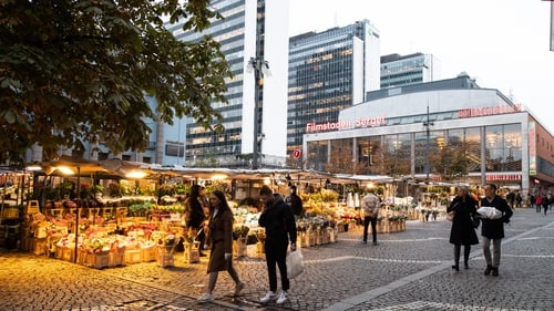 People walk past flower stalls at Hotorget square in central Stockholm