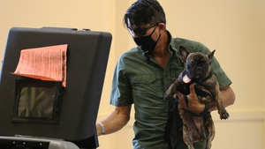 Florida voter Auggie Mejia holding his dog, Baby, casts his ballot in Miami