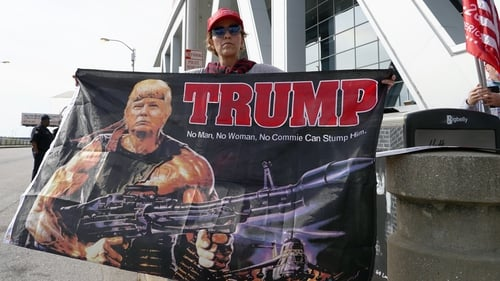 A Trump supporter holds a flag depicting the president as Rambo