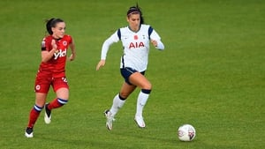 Alex Morgan of Tottenham Hotspur (R) runs with the ball under pressure from Lily Woodham of Reading