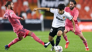 Lee Kang-in of Valencia is tackled by Madrid's Sergio Ramos.