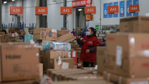 A Chinese warehouse worker checks the delivery information for packages on Singles' Day