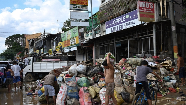 Motorists travel past trash and debris swept up on a bridge in Manila after Typhoon Vamco hit