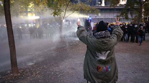 A protester reacts as police use water cannon to disperse a demonstration against coronavirus restrictions yesterday in Frankfurt