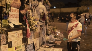 A man stands next to a memorial for the murdered during the massive protests next to National Congress in Lima, Peru