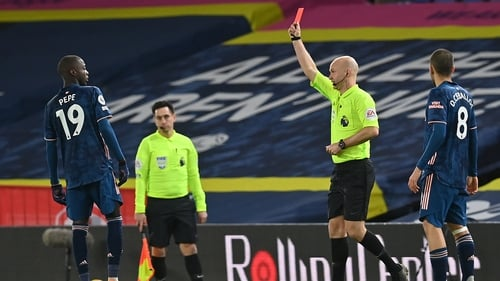 Nicolas Pepe (L) is shown a red card by atch Referee Anthony Taylor