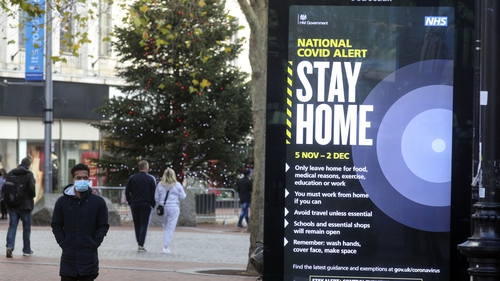 A shopper walks past a government advert on Covid-19 in Reading, England