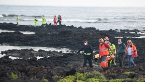 Rescue workers carry a body off Orzola beach in Lanzarote
