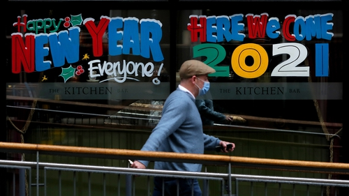 A man walks past a pub window sign in Belfast city centre