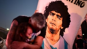 A father and daughter mourn as they gather by the Obelisk in Buenos Aires to pay homage to Diego Maradona