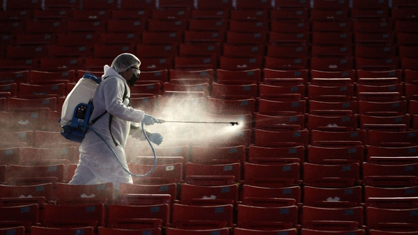 A member of the staff at Akron stadium in Guadalajara, Mexico disinfects the stands before the start of a football match