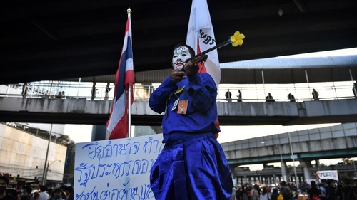 A pro-democracy protester poses with a gun with a flower in the barrel during the Bangkok rally