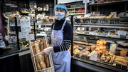 A bakery worker in Paris, France where restrictions on retail are being eased from today