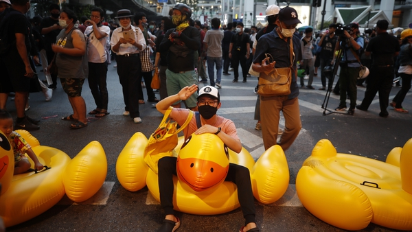 Pro-democracy protesters on inflatable rubber ducks during a protest in Bangkok, Thailand
